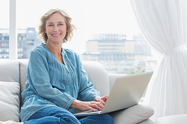 Content blonde woman sitting on her couch using laptop smiling at camera at home in the sitting room