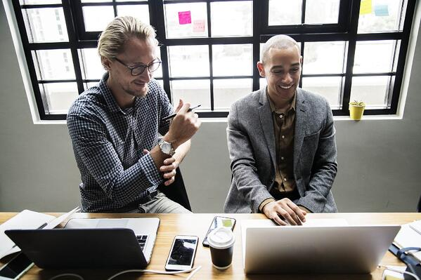 two men on computers using LMS software for leadership development