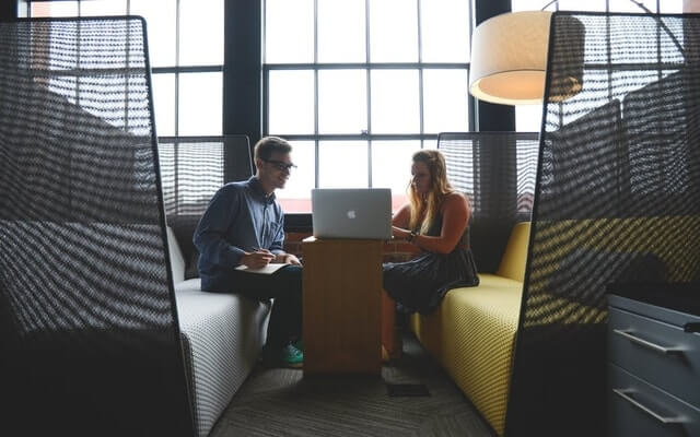 two employee working together on one laptop LMS onboarding.jpg