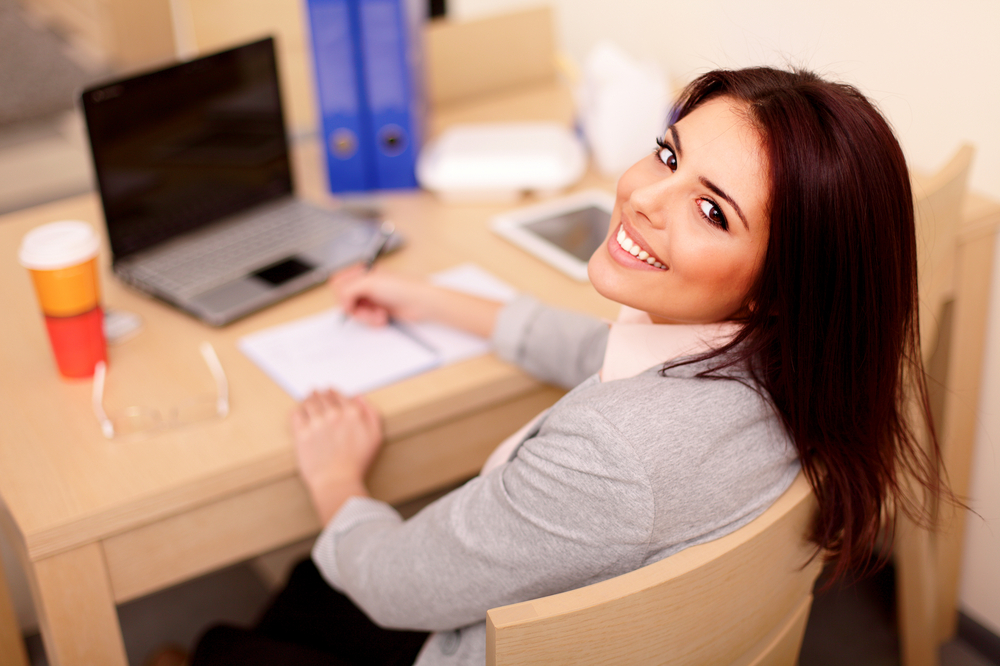 https://f.hubspotusercontent00.net/hubfs/3844305/Stock%20images/Young%20businesswoman%20sitting%20at%20desk%20and%20working.%20Smiling%20and%20looking%20back%20at%20camera.jpeg